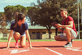 the coach times and gives tips for the ride to his young runner athlete with the tablet