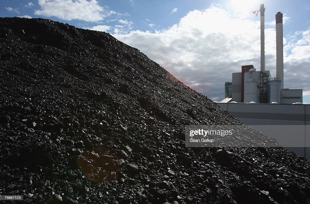 The coal and garbage burning power plant of Statdtwerke Nuemuenster stands behind a mound of coal August 3 2007 in Nuemuenster Germany The plant...
