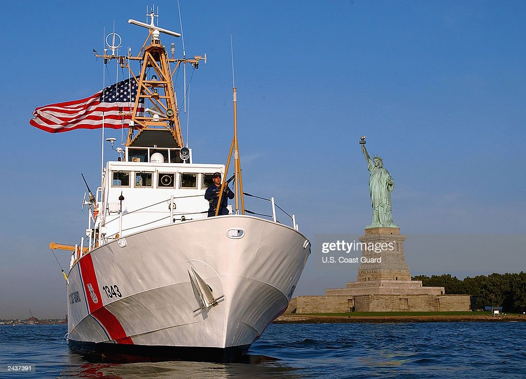 The Coast Guard Cutter Bainbridge Island homeported in Sandy Hook New Jersey stands watch over the Statue of Liberty August 28 2003 in New York Harbor
