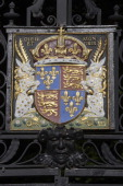 The coat of arms of Edward III wrought iron and enamel on the entrance gate to Trinity College Cambridge Cambdridgeshire United Kingdom
