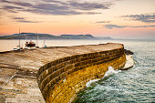 The Cobb, the historic harbour breakwater at Lyme Regis, Dorset, England, on a summer evening.