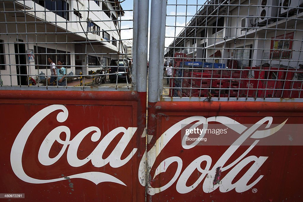 The Coca-Cola Co. logo is displayed on a closed gate at the Coca-Cola Bottlers Philippines Inc. facility in Tacloban, the Philippines, on Monday, Nov. 18, 2013. Super Typhoon Haiyan slammed into the central Philippines on Nov. 8, knocking down most buildings, killing thousands, displacing 4 million people and affecting more than 10 million. Photographer: Paula Bronstein/Bloomberg via Getty Images