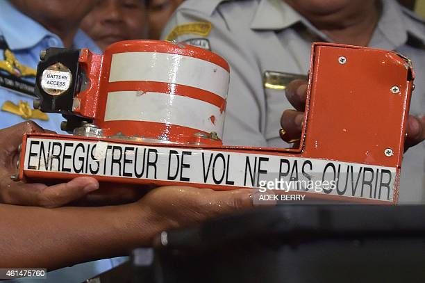 The cockpit voice recorder from AirAsia flight QZ8501 is displayed by officials upon its arrival in Pangkalan Bun on January 13 2015 Indonesian...