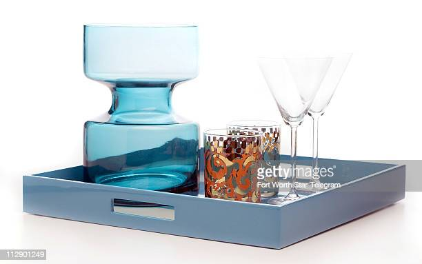 The cocktail hour calls for this handcrafted lacquered wood tray in Tri Blue by Pacific Connection $125 Add a glass turquoise barrel vase $50 as a...
