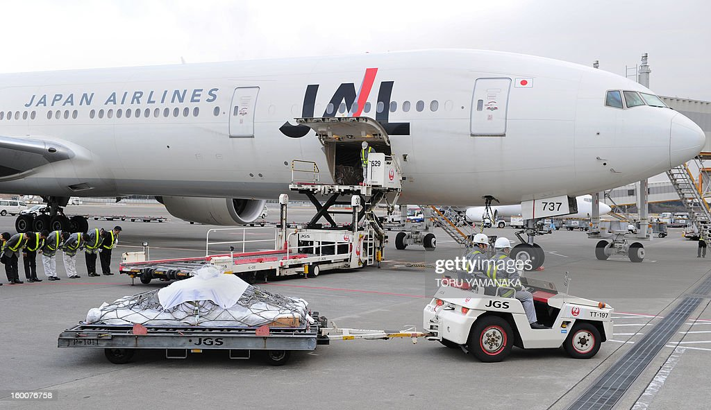 The coffin (front L) carrying the last Japanese victim of the Algerian hostage crisis is transported across the tarmac after it was unloaded from a plane at Narita Airport, outside Tokyo on January 26, 2013. The body of the last of 10 Japanese killed in the Algerian hostage crisis arrived in Japan by commercial flight, a day after the bodies of the nine others returned home with seven Japanese survivors. AFP PHOTO / Toru YAMANAKA