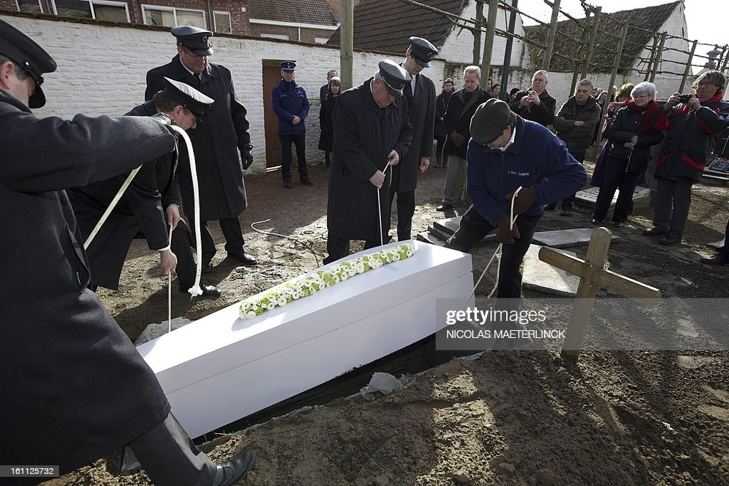 The coffin of Belgian painter Roger Raveel is lifted in a grave by feneral employees during his funeral ceremony, on February 9, 2013 in Machelen-aan-de-Leie. Roger Raveel died on January 30 at the age of 91. MAETERLINCK