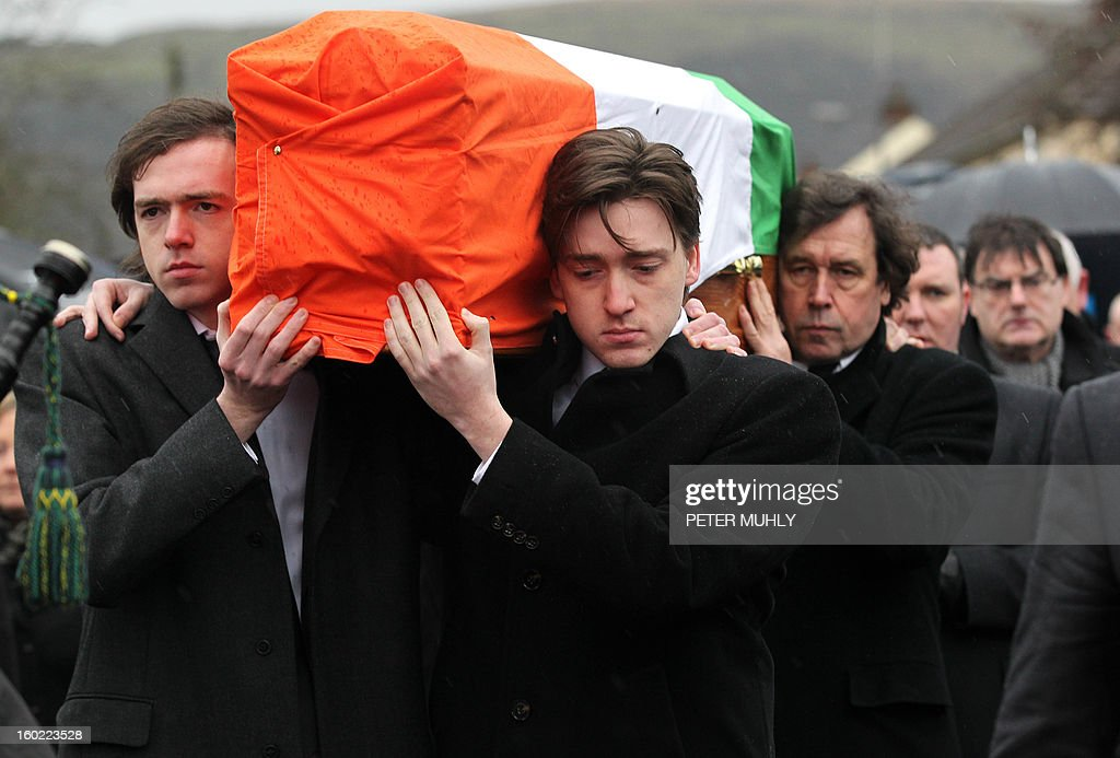 The coffin of convicted Old Bailey bomber Dolours Price is carried by her two sons Danny (L) and Oscar to St Agnes Church in west Belfast, Northern Ireland, on January 28, 2013. Price, convicted for the infamous IRA bombing of the Old Bailey court in London in 1973, was found dead at her home in Ireland, her family said January 24, 2013. Price was one of a number of high-profile IRA members who gave accounts of their past to Boston College in a series of interviews as part of the US university's oral history of the Northern Ireland conflict. AFP PHOTO / PETER MUHLY