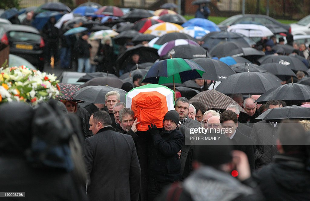 The coffin of convicted Old Bailey bomber Dolours Price is draped with the Irish flag as it is carried to St Agnes Church in west Belfast, Northern Ireland, on January 28, 2013 during her funeral. Price, convicted for the infamous IRA bombing of the Old Bailey court in London in 1973, was found dead at her home in Ireland, her family said January 24, 2013. Price was one of a number of high-profile IRA members who gave accounts of their past to Boston College in a series of interviews as part of the US university's oral history of the Northern Ireland conflict. AFP PHOTO / PETER MUHLY