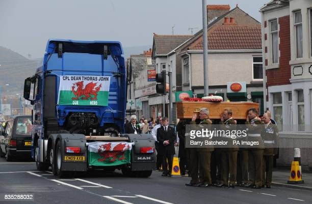 The coffin of Corporal Dean John is carried to the back of a lorry in Port Talbot to be transported to the funeral