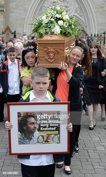 The coffin of Gerry Conlon is carried from St Peter's Cathedral after a requiem mass by family members as 10 year old Padraig McKernan holds a framed...