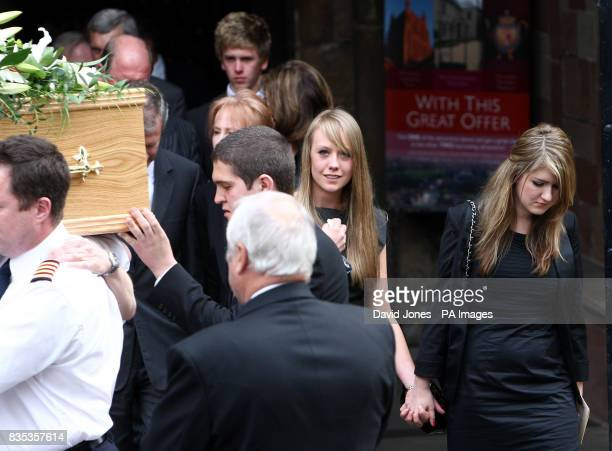 The coffin of helicopter copilot Richard Menzies followed by his girlfriend Katherine Botham and sister Laura Menzies is carried from his funeral...