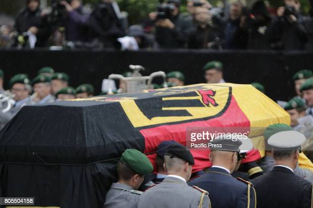 The coffin of Helmut Kohl is carried by eight soldiers past the military guard of honour A funeral mass for the former German Chancellor Helmut Kohl...