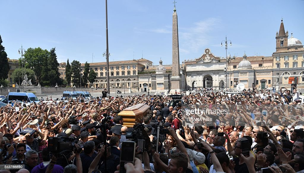 The coffin of Italian actor Bud Spencer, born Carlo Pedersoli, is carried outside the 'church of the artists', Santa Maria in Montesanto, on June 30, 2016 at the end of a ceremony for the funeral of the actor at Piazza del Popolo in Rome. Bud Spencer who starred in a string of spaghetti westerns, died on June 27 in Rome aged 86. Spencer, born in Italy in 1929, played in 16 films alongside Terence Hill, whose real name was Mario Girotti. He was also an Italian swimming champion and in 1950, he became the first Italian to swim the 100-metre freestyle in under a minute. / AFP / TIZIANA
