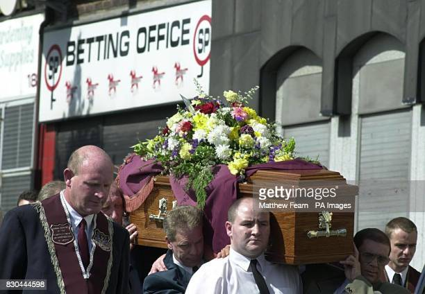 The coffin of murder victim Bobby Mahood is carried past the betting shop in Crumlin Road Belfast on its way to Carnmoney Cemetary Several hundred...