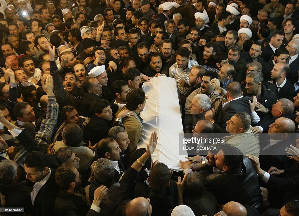 The coffin of Sunni Muslim cleric Mohamed Saeed al-Bouti, who died in a suicide bomb attack, is carried during his funeral ceremony on March 23, 2013 at the Omayyad mosque in Damascus, Syria. The suicide bomb attack in a mosque in Damascus has killed 42 people on March 21, including Saeed al-Bouti, wounding dozens of others, Syrian health ministry said.