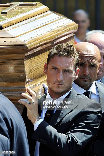 The coffin of the AS Roma football club president Franco Sensi is carried out by his player captain Francesco Totti and Roma's coach Luciano...