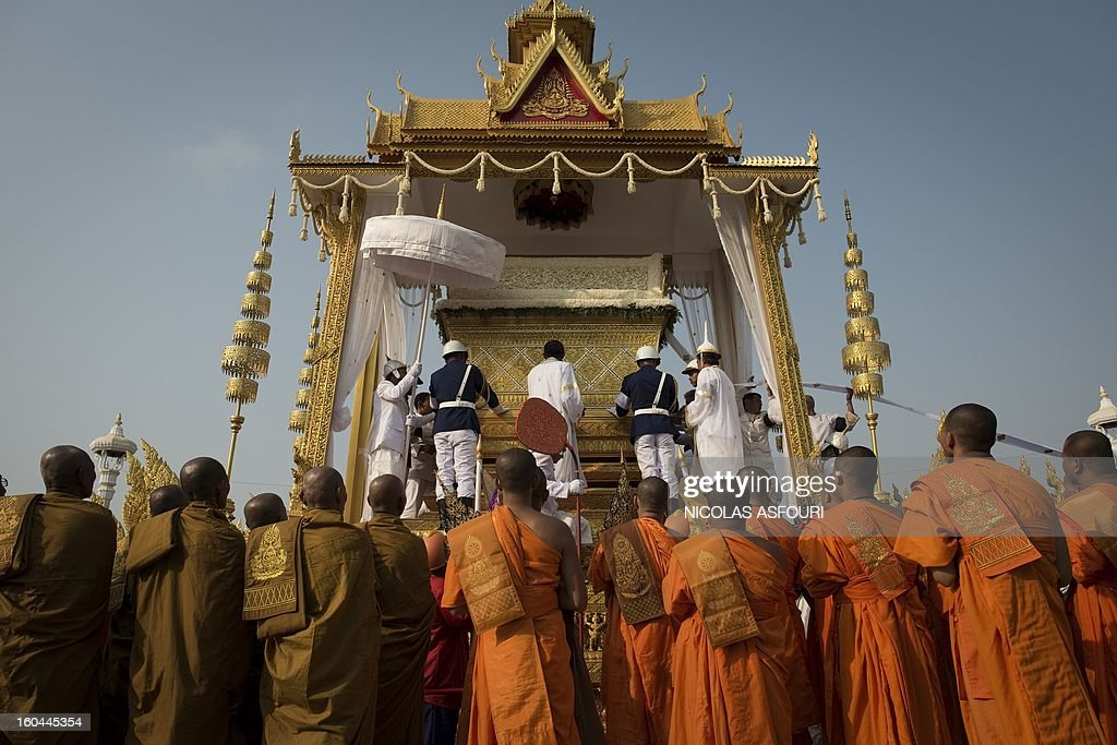 The coffin of the late former King Norodom Sihanouk is lifted onto a chariot in front of the Royal Palace during his funeral procession in Phnom Penh on February 1, 2013. Sihanouk, who abdicated in 2004 after steering Cambodia through six decades marked by independence from France, civil war, the murderous Khmer Rouge regime and finally peace, died of a heart attack in Beijing on October 15, 2012 and will be cremated on February 4. AFP PHOTO / Nicolas ASFOURI