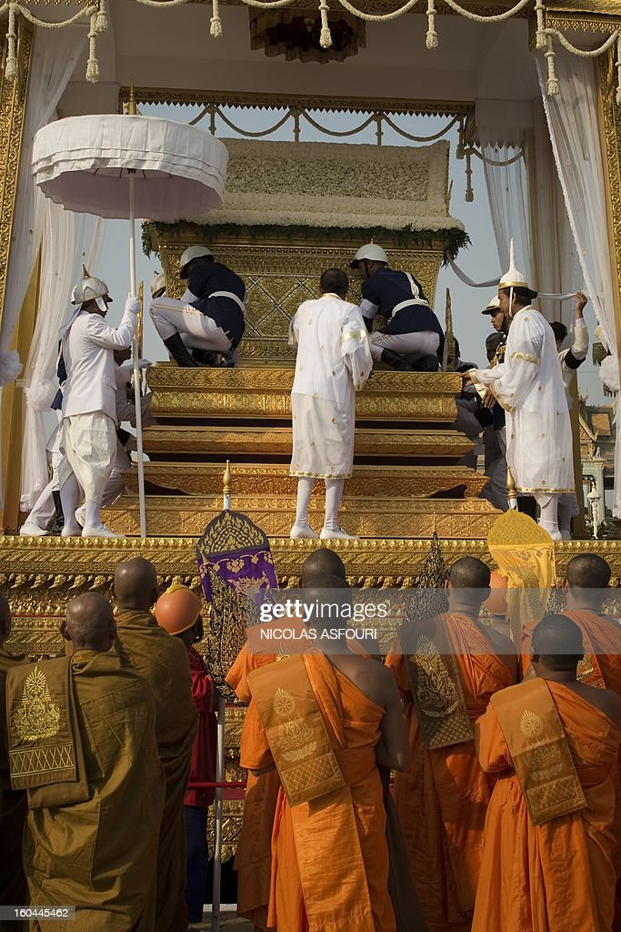 The coffin (up) of the late former King Norodom Sihanouk is lifted onto a chariot in front of the Royal Palace during his funeral procession in Phnom Penh on February 1, 2013. Sihanouk, who abdicated in 2004 after steering Cambodia through six decades marked by independence from France, civil war, the murderous Khmer Rouge regime and finally peace, died of a heart attack in Beijing on October 15, 2012 and will be cremated on February 4. AFP PHOTO / Nicolas ASFOURI