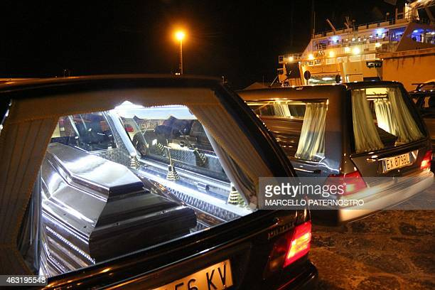 The coffins with the bodies of immigrants who died trying to reach the Italian coast arrive from Lampedusa on February 11 2015 in Porto Empedocle...