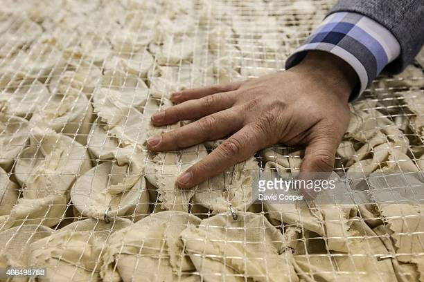 The coil springs in cotton pockets are placed into the mattress Brad Warner managing partner of Marshall Mattress and his son Eric give us a tour and...