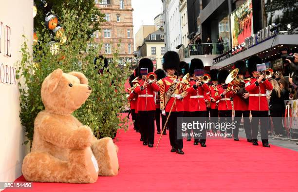 The Coldstream Guard brass band march past a giant teddy bear during the world premiere of Goodbye Christopher Robin at the Odeon in Leicester Square...