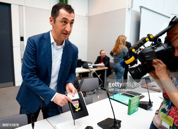 the coleader of German Greens Party 'BÜNDNIS 90/DIE GRÜNEN' Cem Oezdemir shows a plaque with the logo of the German Bundesliga club VfB Stuttgart as...