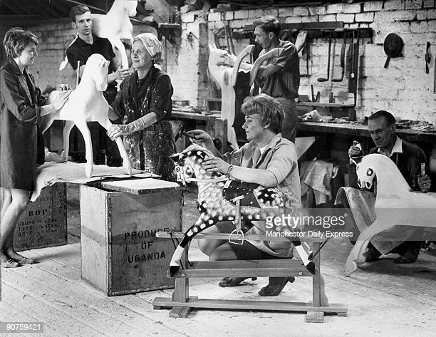 The Collinson family in their workshop in Smithdown Road Ivy and Mrs Collinson Senior sanding a horse Jervis carrying a horse on his shoulder Leonard...