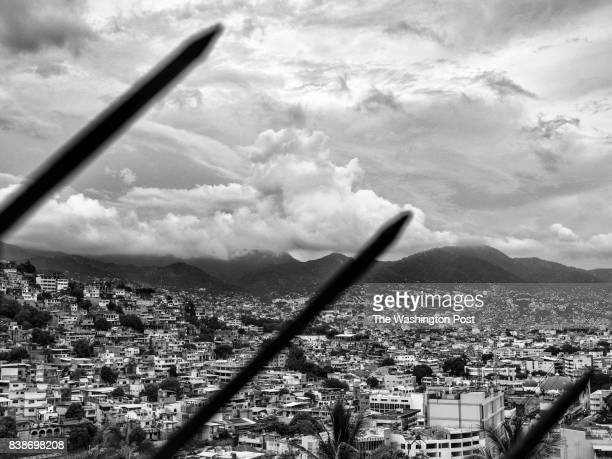 The colonias or impoverished neighborhoods are seen through an iron fence in Acapulco Mexico on July 22 2017 Acapulco is considered the fourth most...