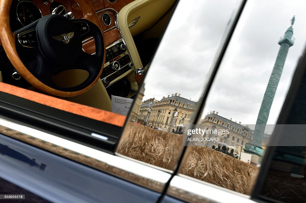 The Colonne Vendome is reflected on a Bentley car during the instalation of French artist Gad Weil's temporary piece of art the 'Bles Vendome' at the place Vendome in Paris on July 1, 2016. / AFP / ALAIN