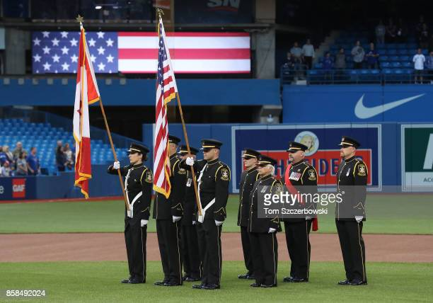 The Color Guard holds Canadian and American flags on the field during the playing of the American national anthem on the sixteenth anniversary of...