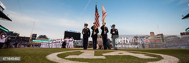 The Color Guard stands at attention during the National Anthem before the Opening Night game between the Chicago Cubs and the St Louis Cardinals at...