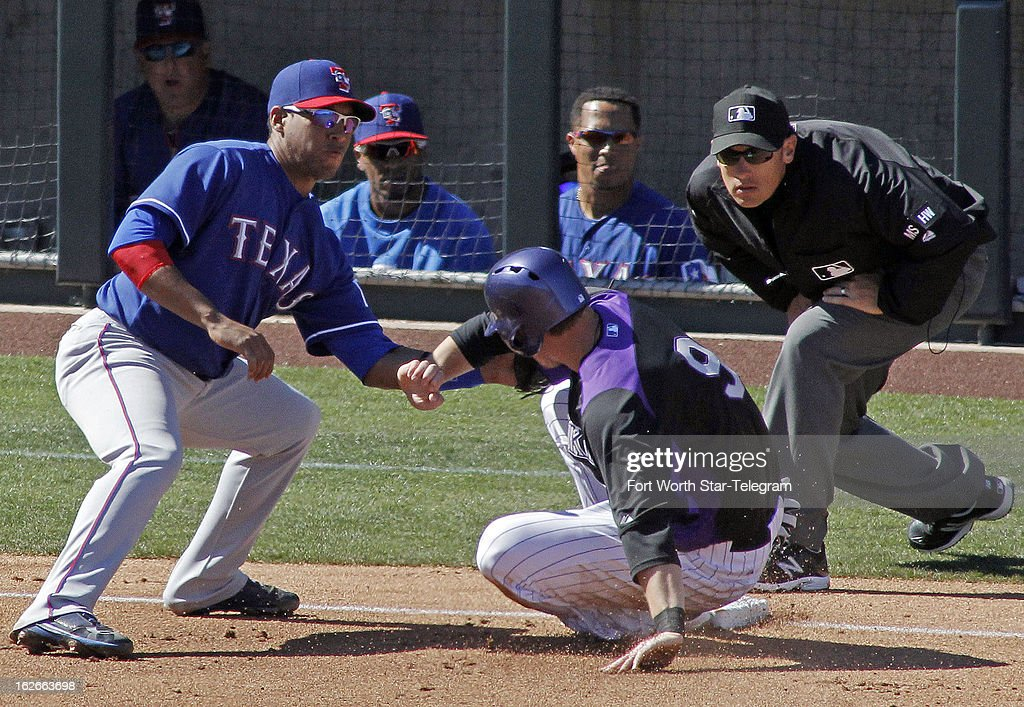 The Colorado Rockies' DJ LeMahieu (9) slides into third base as Texas Rangers Rangers third baseman Yangervis Solarte waits on the throw from center field in the third inning of a spring training game in Scottsdale, Arizona, Monday, February 25, 2013. LeMahieu beat the throw to the base. The Rockies beat the Texas Rangers 9-1.