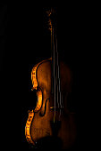 A violin laced against a black background. The Sidelight creates a negative space, leaving the views to picture the other half of the the violin.