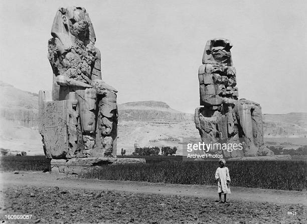 The Colossi of Memnon two giant statues of Pharaoh Amenhotep III built in the 14th century BC at the Theban necropolis Egypt circa 1920