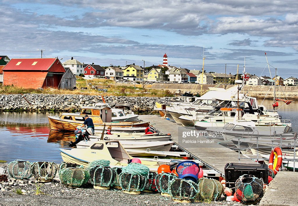 The colourful harbour of Alnes, Norway with lobster pots and fishing boats with the lighthouse in the background.