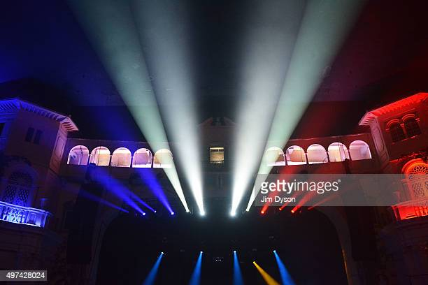 The colours of the French flag are projected in tribute to the victims of the Paris terror attacks prior to New Order performing live on stage at...