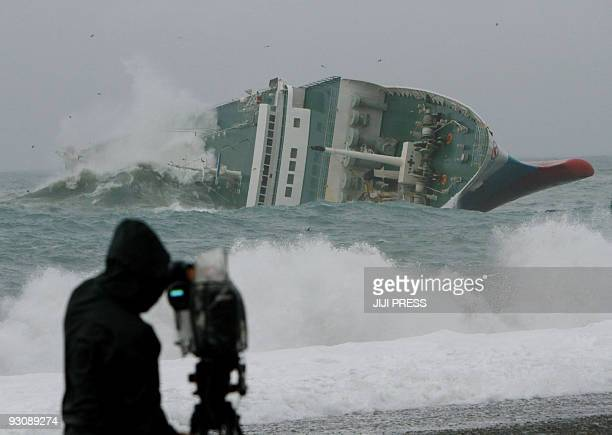 The commercial ferry Ariake carrying 3300 tonnes of cargo and 28 passengers and crew lists to starboard in a storm in the Pacific Ocean off the coast...