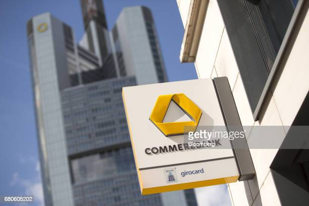 The Commerzbank AG logo sits outside a bank branch as the Commerzbank skyscraper headquarters stands beyond in Frankfurt Germany on Tuesday May 9...