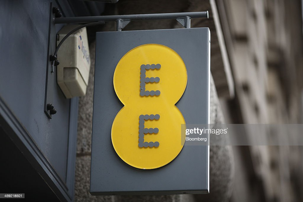 The company logo hangs on a sign outside an EE mobile phone store in London, U.K., on Tuesday, Dec. 24, 2013. Vodafone Group Plc; EE, which is co-owned by Orange SA and Deutsche Telekom AG; Three, owned by Hutchison Whampoa Ltd.; and Virgin Media Inc. said they will cap bills run up on phones reported lost or stolen, stop mid-contract price increases, and support the U.K. government in its attempt to end roaming charges within the European Union. Photographer: Simon Dawson/Bloomberg via Getty Images