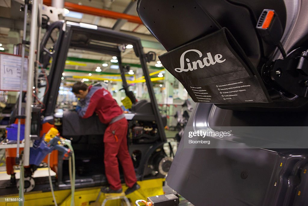 The company logo sits attached to a seat of a Linde E25 electric forklift truck as an employee works on the production line at the Linde Material Handling GmbH factory, a unit of Kion Group AG, in Aschaffenburg, Germany, on Tuesday, Nov. 12, 2013. Kion Group AG, the German forklift-maker which listed shares in June, is looking to expand its global sales network via acquisitions to catch up with main competitor Toyota Industries Corp. Photographer: Krisztian Bocsi/Bloomberg via Getty Images