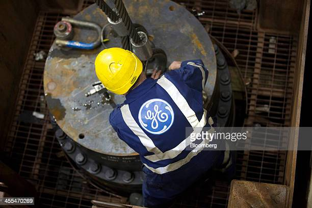 The company logo sits on an employee's overalls as he secures a metal cable to a section of a subsea oil and gas tree at the General Electric Co...