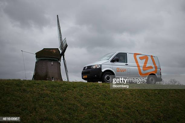 The company logo sits on the side of a Ziggo NV truck as it stands on a dike with a windmill beyond in this arranged photograph in Heerhugowaard...