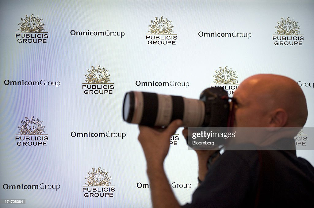 The Company logos for Publicis Groupe SA and Omnicom Group Inc are seen behind a photographer during a news conference at the Publicis headquarters in Paris, France, on Sunday, July 28, 2013. Publicis Groupe SA and Omnicom Group Inc. agreed to merge in an all-stock transaction to create the world's largest advertising company with $23 billion in revenue, toppling market leader WPP Plc. Photographer: Balint Porneczi/Bloomberg via Getty Images