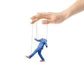 The concept of corporate slavery. A hand controls a worker on a white background. Submission of will. Puppet master.