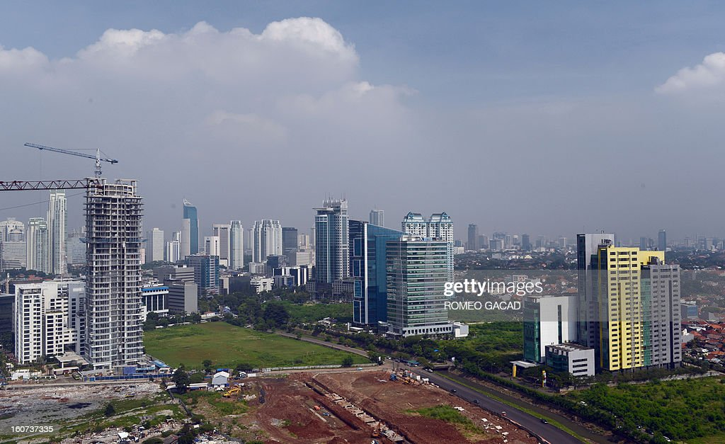 The construction of a new high rise building (L) rises over the skyline of Jakarta on February 5, 2013. Indonesia said on February 5 that Southeast Asia's biggest economy grew 6.23 percent in 2012 , below expectations, supported by strong private consumption and investment.