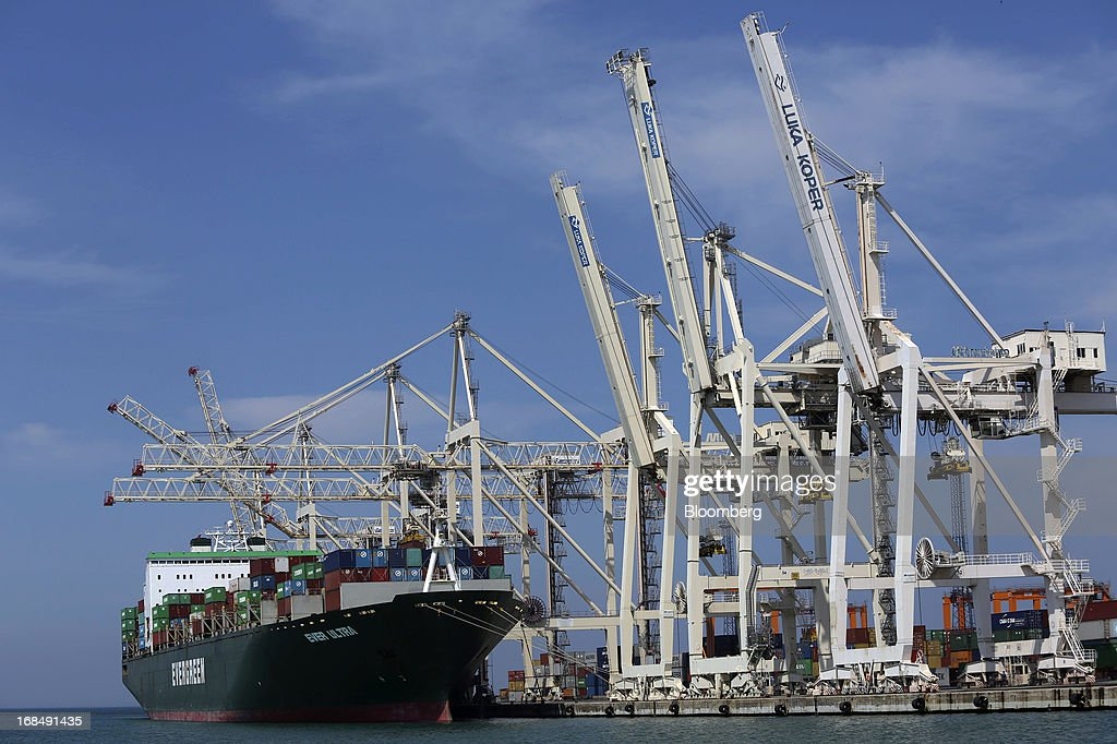 The container ship 'Ever Ultra,' operated by Evergreen Marine Corp Taiwan Ltd., stands beneath gantry cranes at the dockside in the port of Koper, operated by Luka Koper d.d., in Koper, Slovenia, on Thursday, May 9, 2013. The former Yugoslav nation, mired in its second recession since 2009, will contract this year and next, according to a May 3 report by the European Commission. Photographer: Chris Ratcliffe/Bloomberg via Getty Images