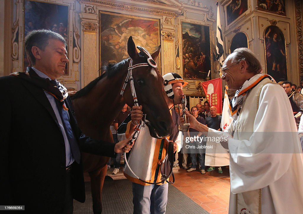 The Contrada della Lupa gathers in its church for the benediction of horse and rider before the annual Palio dell'Assunta horse-race on August 16, 2013 in Siena, Italy. The Palio races in Siena, in which riders representing city districts compete,and takes place twice a year in the summer in a tradition that dates back to 1656.