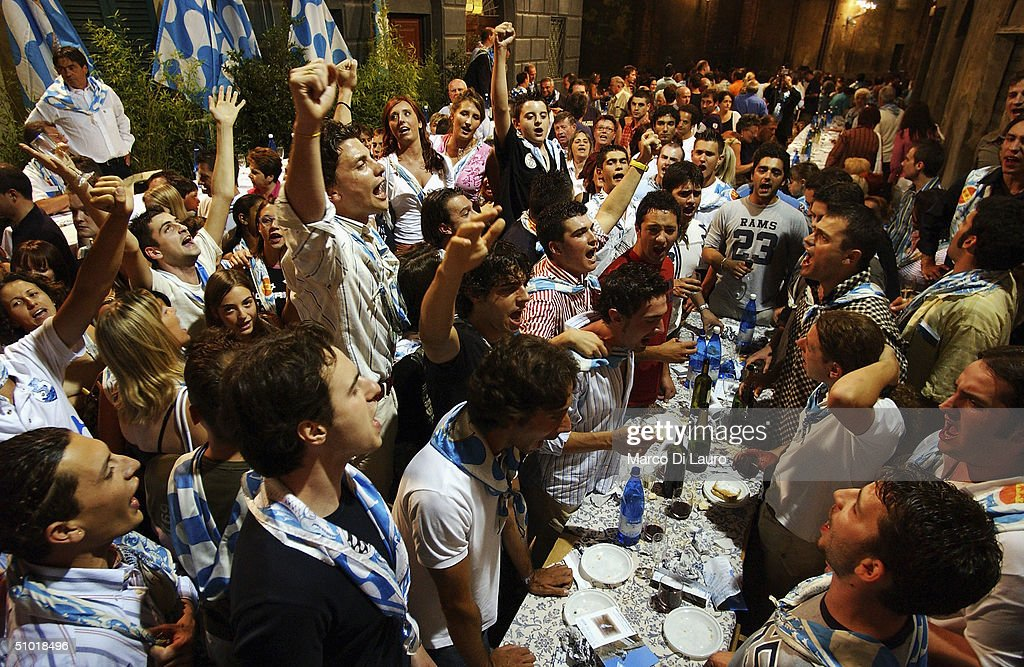 The Contradaioli belonging to the Onda (Wave) one of the seventeen contrade, gather together in the heart of the Contrada, where they have a large dinner to favour the outcome of the race after the fifth trial called 'genera trial, on July 1, 2004 in Siena, Italy. The city's 17 separate Contrade or neighbourhoods vie to compete in the prestigious Palio race, which takes place at the end of a week of festivities which encourage huge support and fierce competition between the participants.