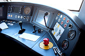 Red button of emergency brake and keys from the door of the train lying on the control panel in the cabin of train