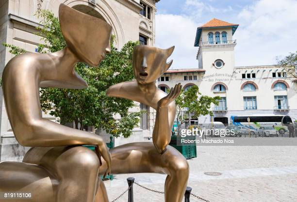 'The Conversation' sculpture by Etienne in old Havana The modernist golden metal sculpture shows two human figures without torsos sitting and talking